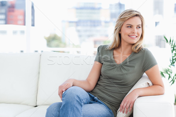 A woman looking sideways with her legs crossed and smiling. Stock photo © wavebreak_media