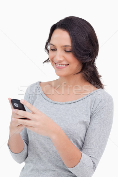 Close up of smiling woman reading text message against a white background Stock photo © wavebreak_media
