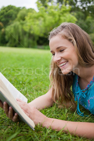 Young girl reading a book in a parkland while lying on the grass and laughing Stock photo © wavebreak_media
