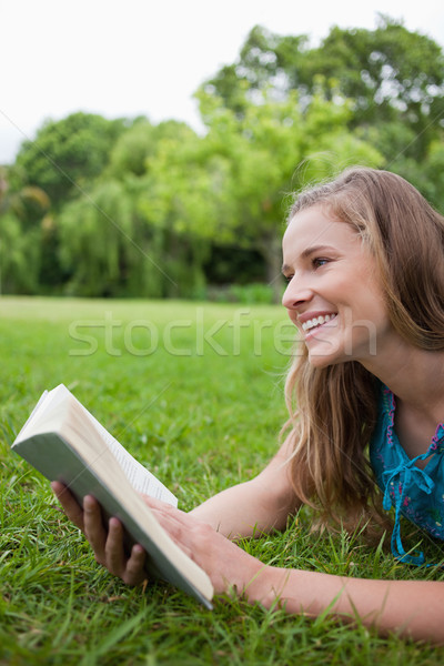 Young smiling woman lying in a parkland while holding a book and looking away Stock photo © wavebreak_media
