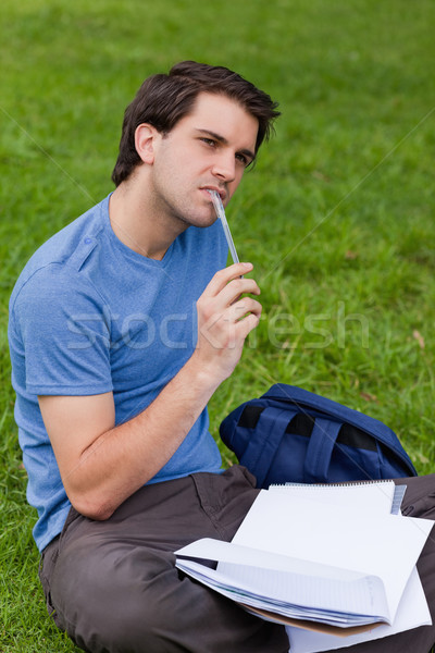 Young thoughtful man holding his ballpoint pen while sitting on the grass in a park Stock photo © wavebreak_media