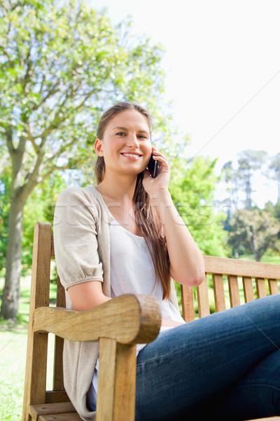 Mosolyog fiatal nő telefon park pad szépség Stock fotó © wavebreak_media