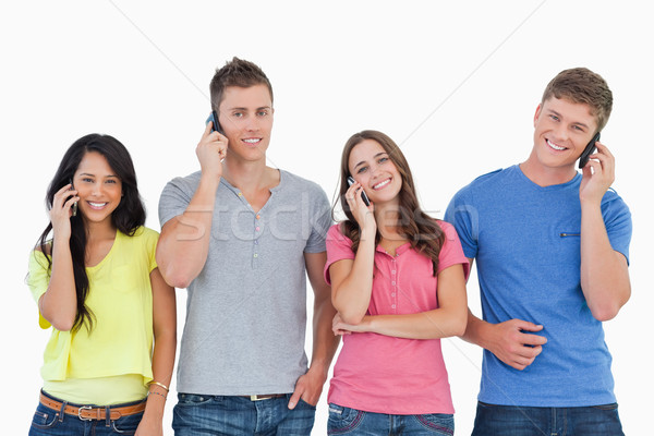 A group of friends of smiling as they all make calls and look into the camera  Stock photo © wavebreak_media