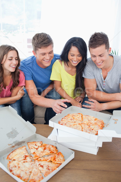 A group of friends with some pizza as one guy reaches out for a slice Stock photo © wavebreak_media