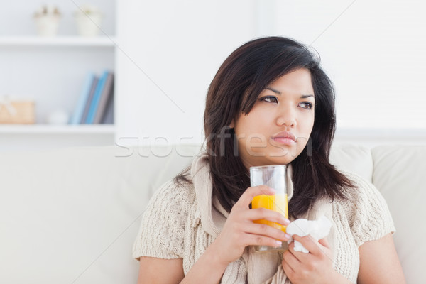Stock photo: Sick woman holding a glass of orange juice in a living room