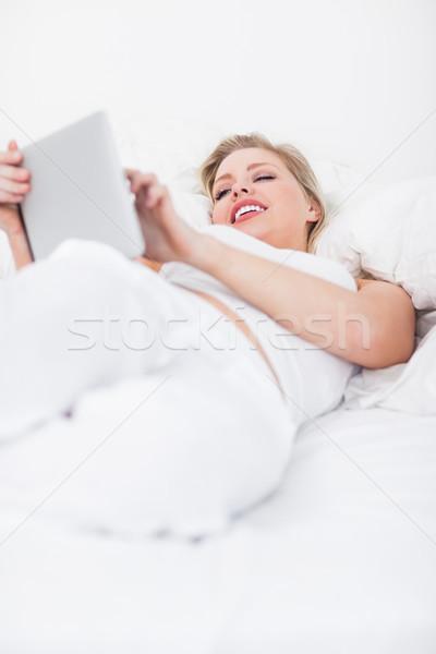 Sorridente ebook leitor cama leitura Foto stock © wavebreak_media