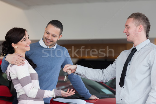 Couple embracing while receiving keys from a salesman in a car shop Stock photo © wavebreak_media