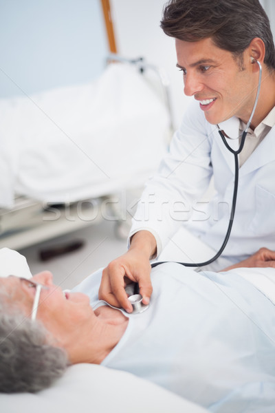 Doctor smiling while auscultating a patient in hospital ward Stock photo © wavebreak_media