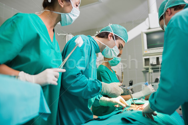 Surgeon using surgical tool in an operating theatre Stock photo © wavebreak_media