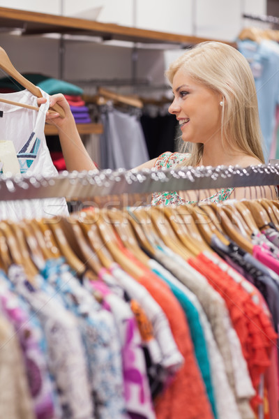 Woman standing at the clothes rack of a boutique showing clothes Stock photo © wavebreak_media