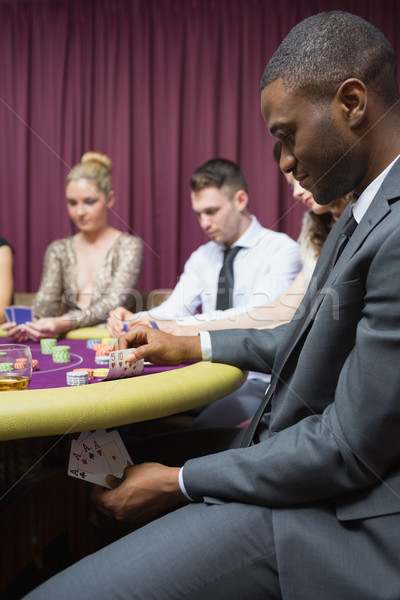 Man looking at four of a kind hand under table in casino Stock photo © wavebreak_media