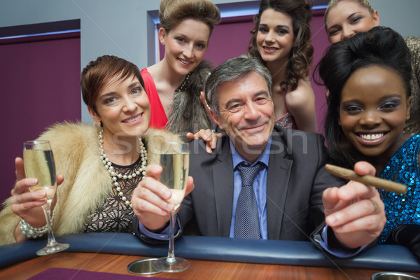 Happy man surrounded by women at roulette table in casino Stock photo © wavebreak_media