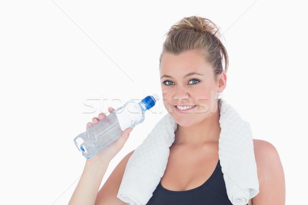 Uśmiechnięta kobieta butelki wody pitnej treningu Zdjęcia stock © wavebreak_media