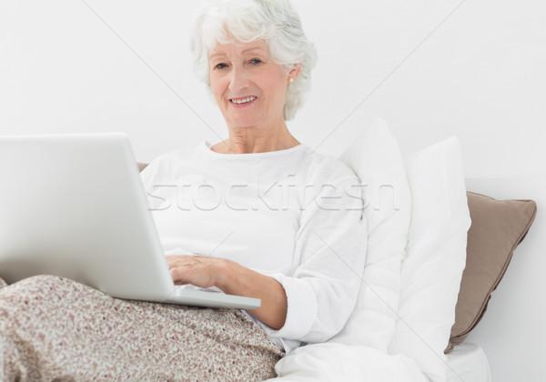 Uśmiechnięty wpisując laptop sypialni komputera Zdjęcia stock © wavebreak_media