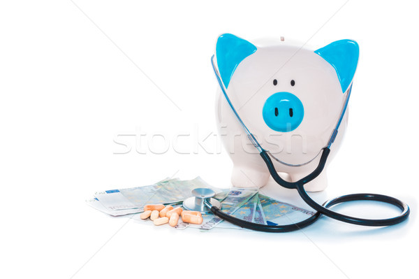 Piggy bank sitting on pile of dollars with stethoscope and pills Stock photo © wavebreak_media