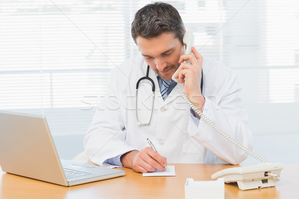 Doctor using phone while writing notes at medical office Stock photo © wavebreak_media