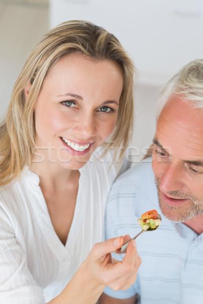 Happy woman feeding her partner a spoon of vegetables Stock photo © wavebreak_media