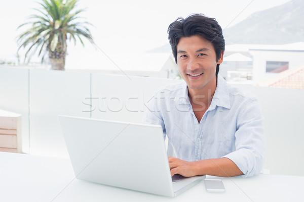улыбаясь человека используя ноутбук за пределами балкона компьютер Сток-фото © wavebreak_media