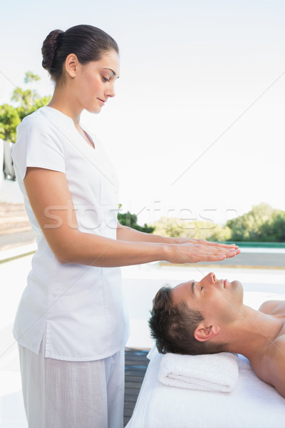 Peaceful man getting reiki treatment poolside Stock photo © wavebreak_media