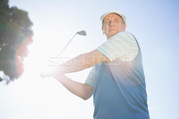 Golfer taking a shot and smiling Stock photo © wavebreak_media