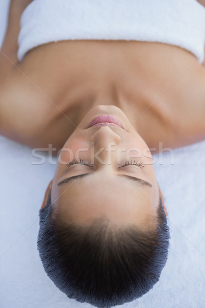 Peaceful brunette lying with eyes closed on a towel Stock photo © wavebreak_media