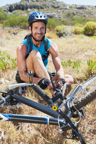 Fit cyclist tying his shoelace on mountain trail smiling at came Stock photo © wavebreak_media