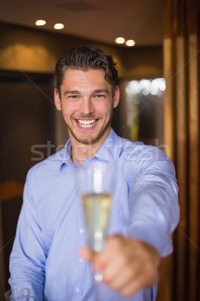 Handsome man holding flute of champagne Stock photo © wavebreak_media