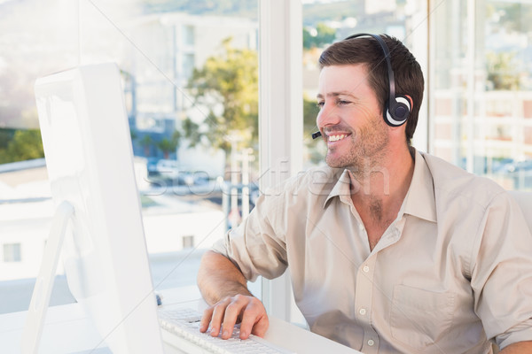 Smiling casual businessman listening to computer at desk Stock photo © wavebreak_media