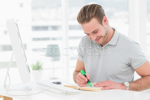 Happy casual businessman highlighting a book Stock photo © wavebreak_media