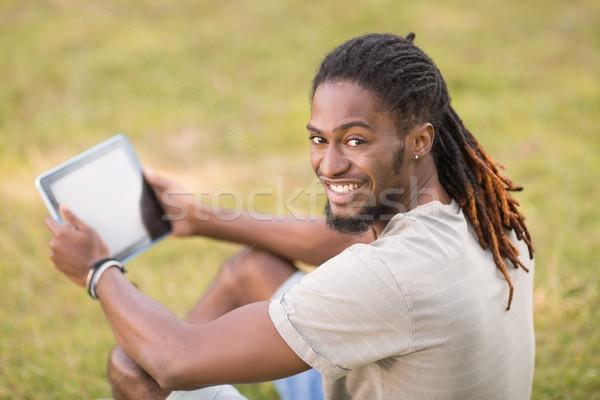 Handsome hipster using his tablet pc Stock photo © wavebreak_media