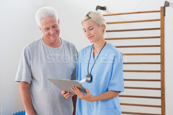 Therapist showing clipboard to senior man  Stock photo © wavebreak_media
