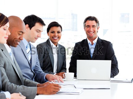 Businessman using laptop with colleagues behind Stock photo © wavebreak_media