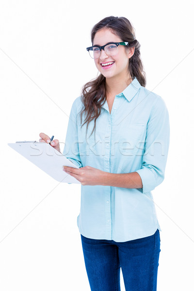 Pretty geeky hipster writing on notebook and smiling at camera Stock photo © wavebreak_media