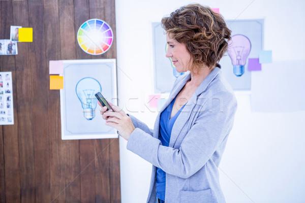 Stock photo: Creative businesswoman using her smartphone