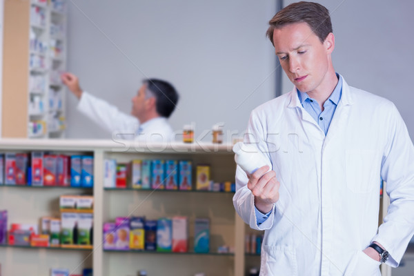 Concentrating pharmacist reading label on medicine jar Stock photo © wavebreak_media