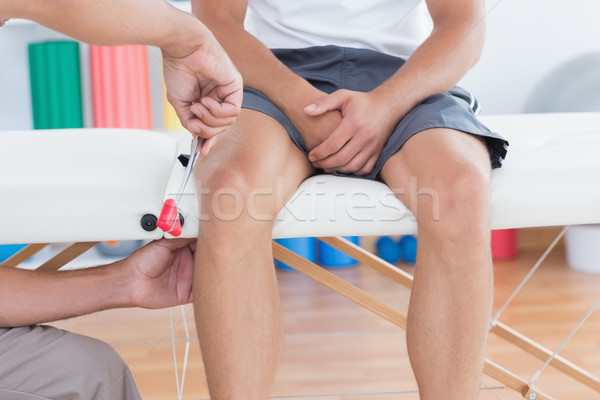 Doctor checking reflexes of the knee of his patient Stock photo © wavebreak_media