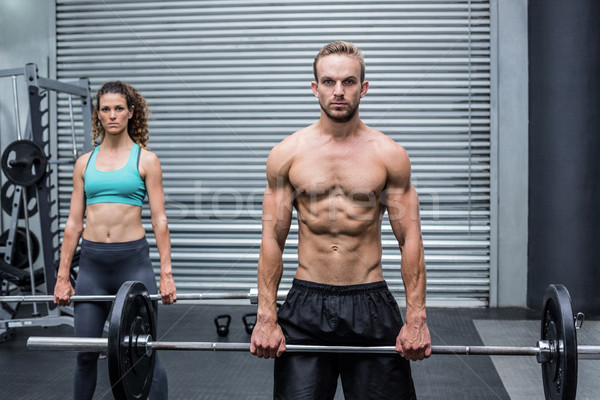 Stock photo: Muscular couple lifting weight together