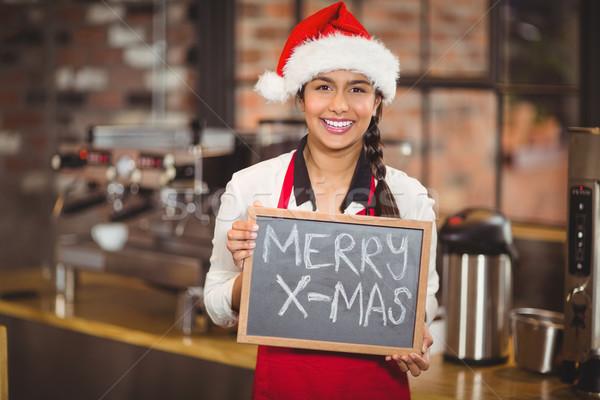 Pretty waitress with a chalkboard merry x-mas Stock photo © wavebreak_media