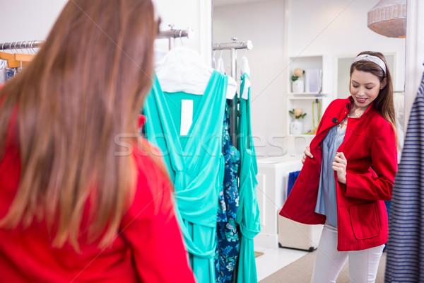 Brunette trying on a red coat Stock photo © wavebreak_media