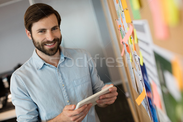 Portrait of young businessman holding digital tablet by soft board Stock photo © wavebreak_media