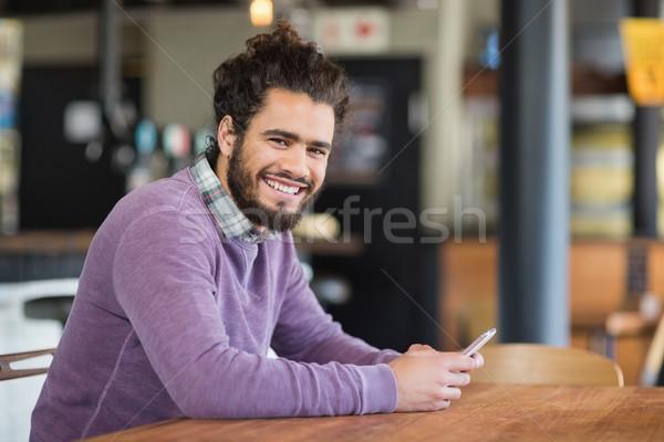 Portrait of man using mobile phones while sitting in restaurant Stock photo © wavebreak_media