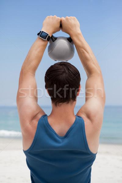 Stock photo: Rear view of young man lifting kettlebell at beach