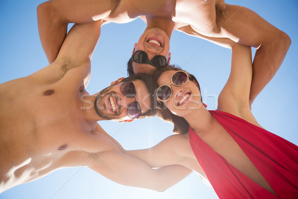 Directly below shot of smiling young friends huddling against clear blue sky Stock photo © wavebreak_media