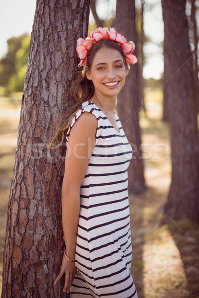 Smiling young woman leaning on tree in forest Stock photo © wavebreak_media