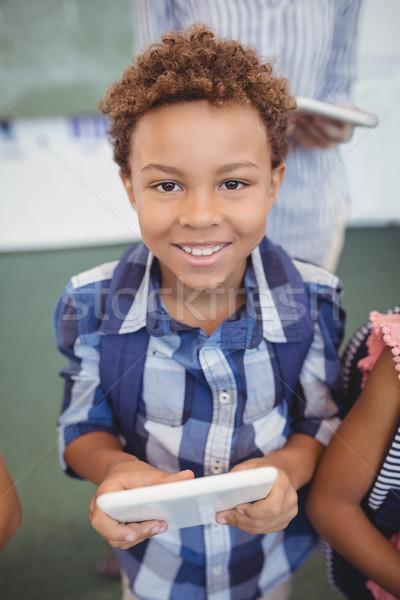 Portrait of cute schoolboy standing with digital tablet Stock photo © wavebreak_media