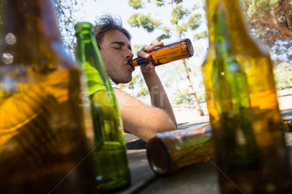 Homem potável cerveja garrafa parque inconsciente Foto stock © wavebreak_media