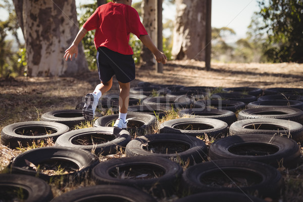 Boy running over tyres during obstacle course Stock photo © wavebreak_media