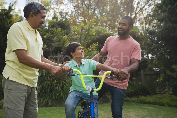 Happy father and grandfather with boy riding bicycle Stock photo © wavebreak_media