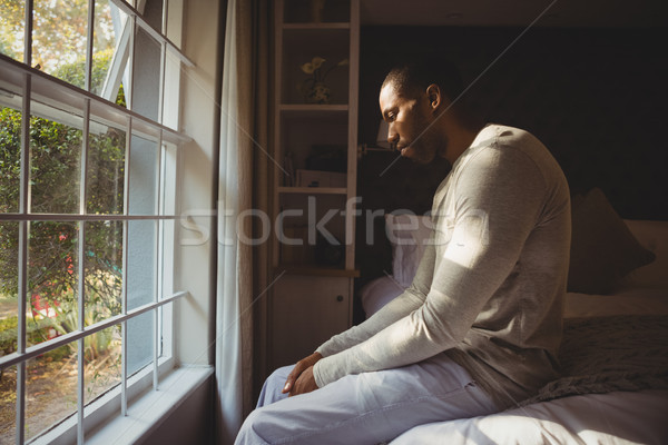Stock photo: Side view of sad man sitting on bed by window