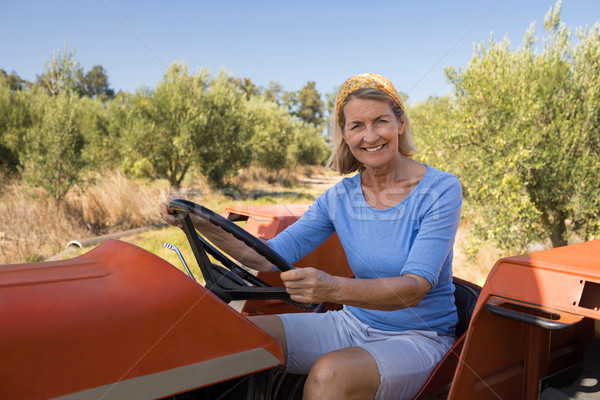 Portrait of happy woman sitting in tractor Stock photo © wavebreak_media